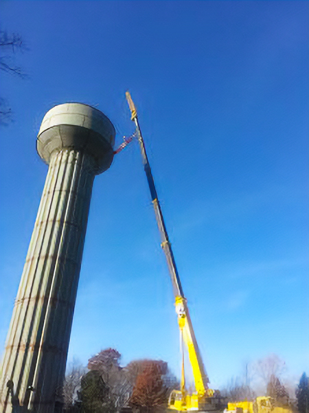 Crane reaching to the top of a water tower