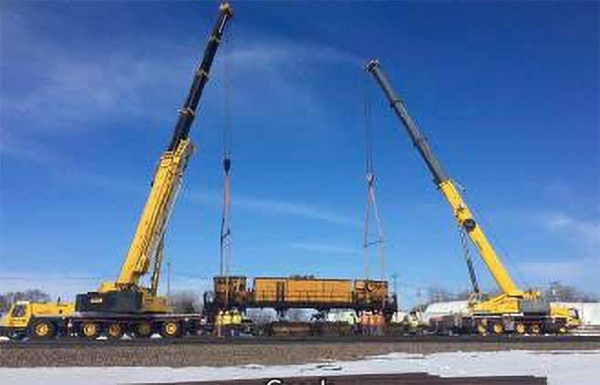 Two cranes lifting train car onto train tracks
