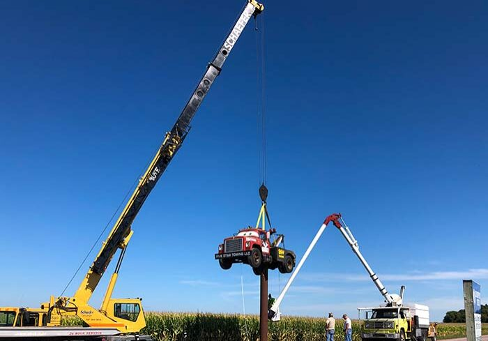 Schaefer Crane Service lifting a tow truck and placing it on top of a sign pole for display